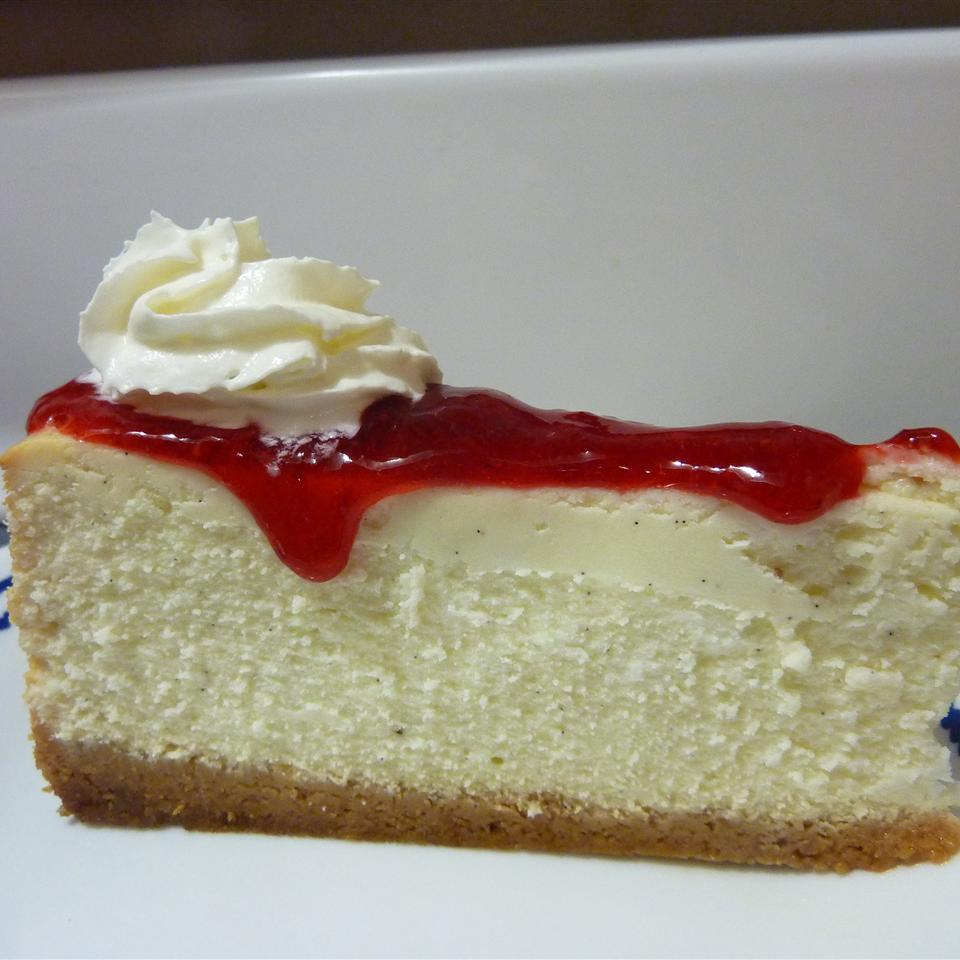 slice of chevre cheesecake topped with berry compote and whipped cream