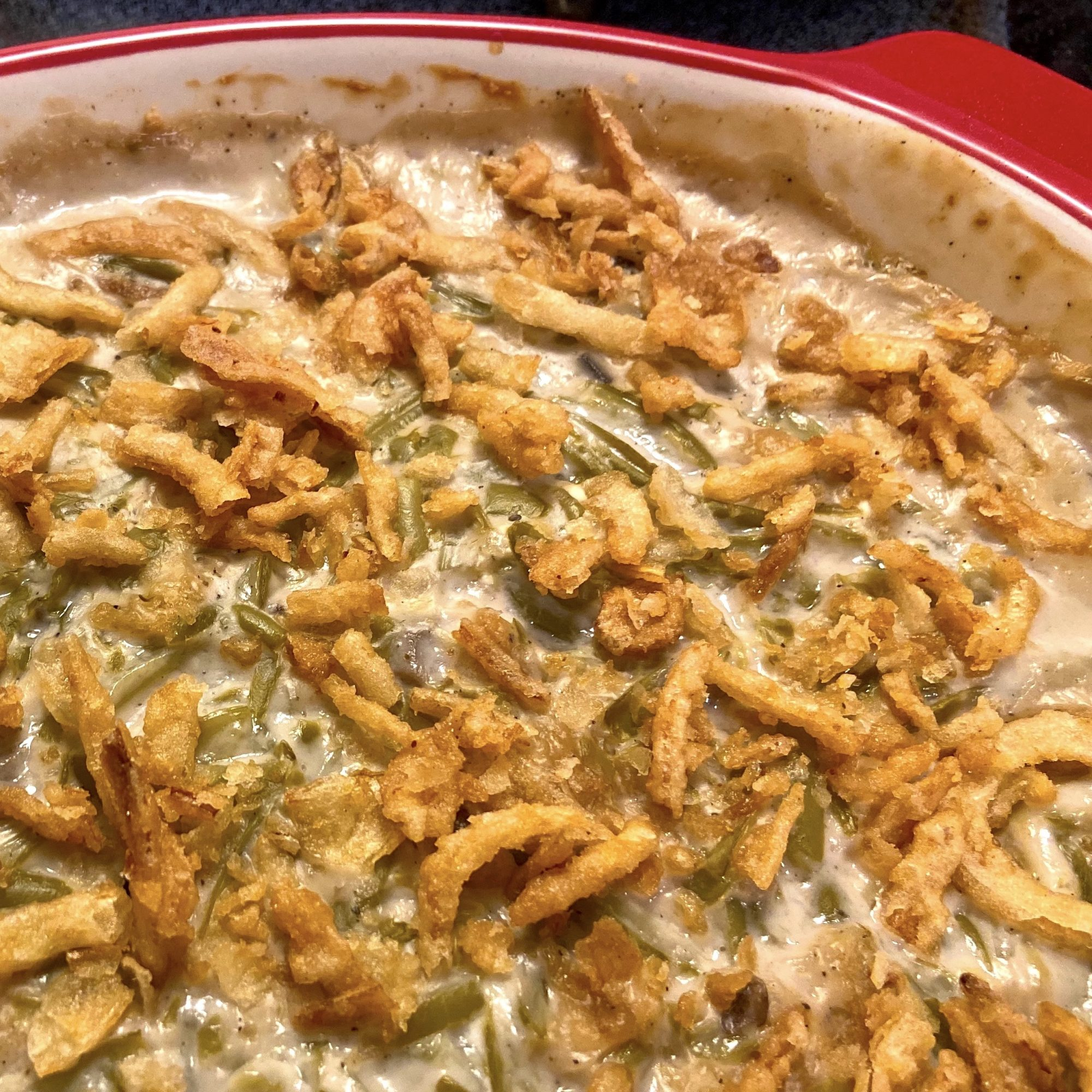 green bean casserole with fried onions in a red casserole dish