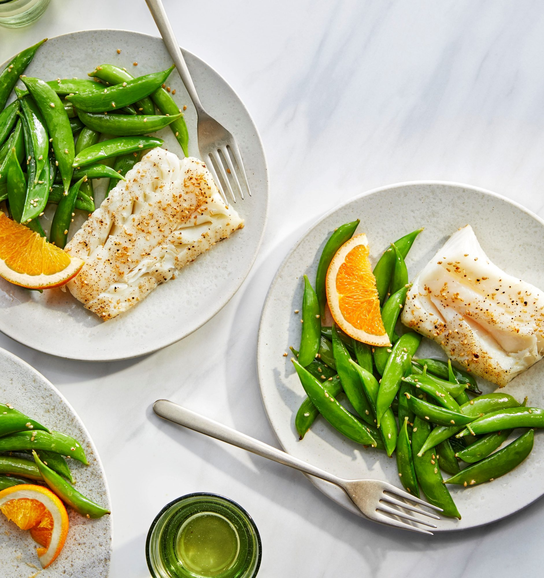 two plates of cod and snap peas garnished with orange wedges