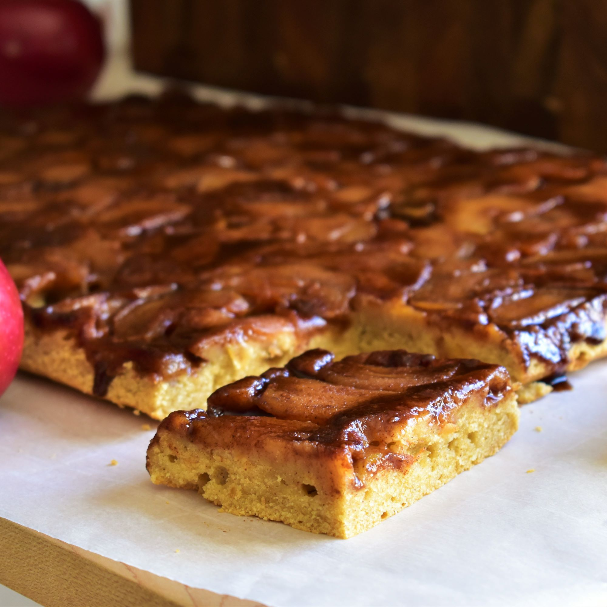 slices of apple cake baked in a sheet pan, with dark brown caramelized apple slices on top