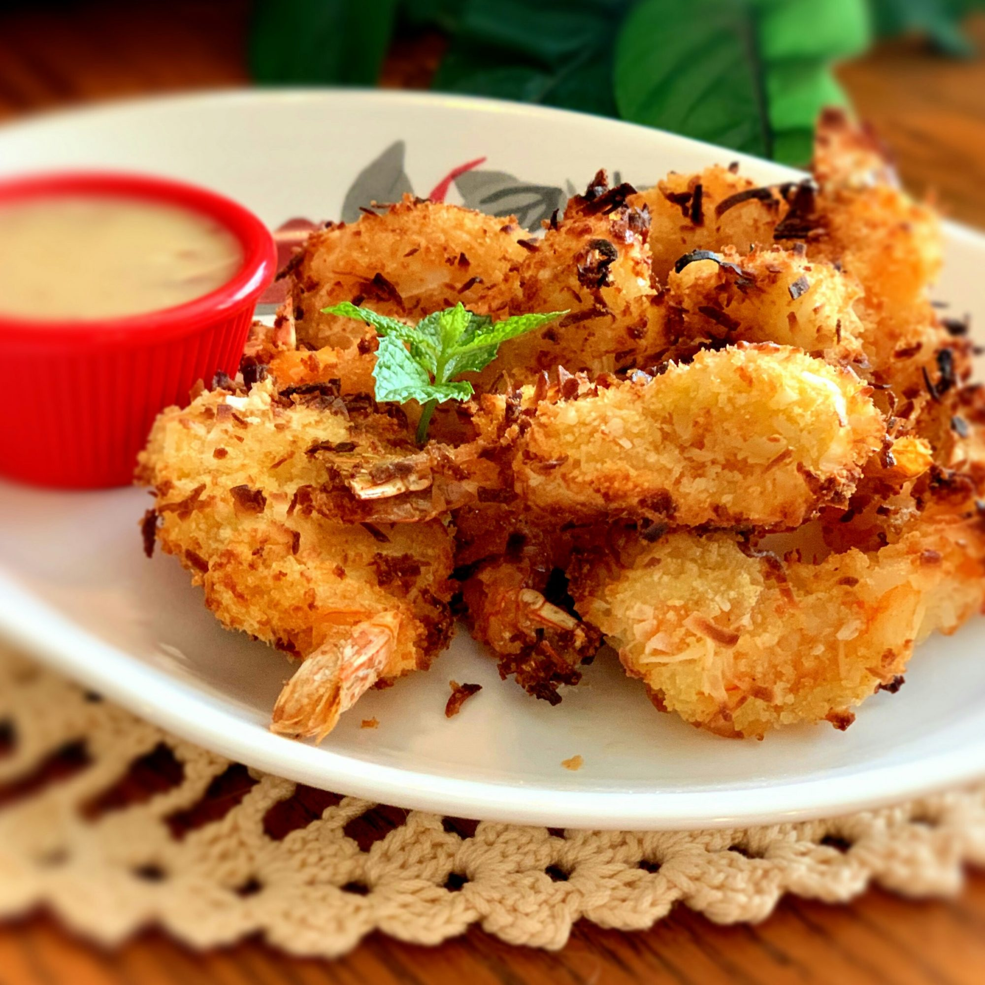 air-fried coconut shrimp with dipping sauce on a white plate