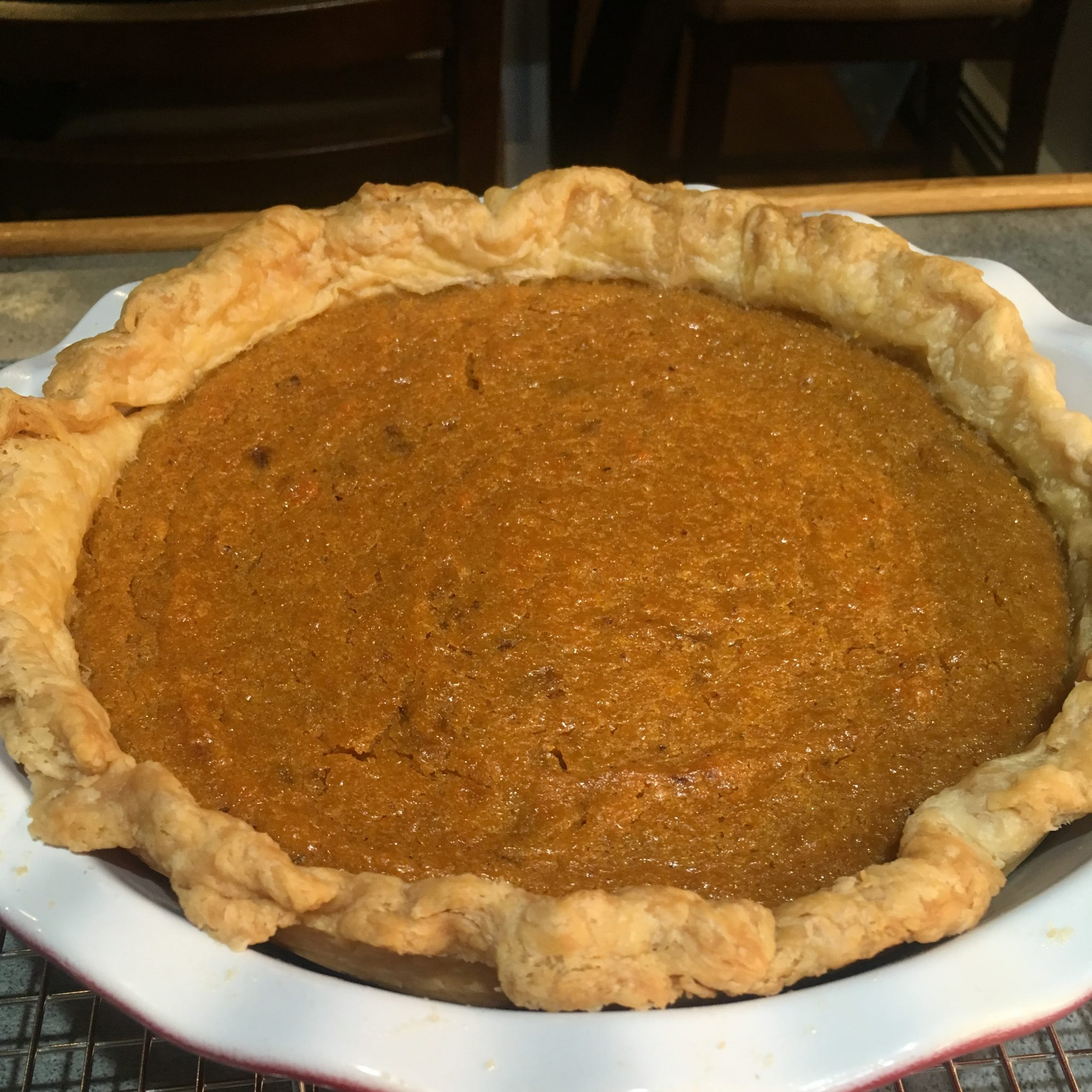 a whole pie with a homemade crust in a ceramic pie plate
