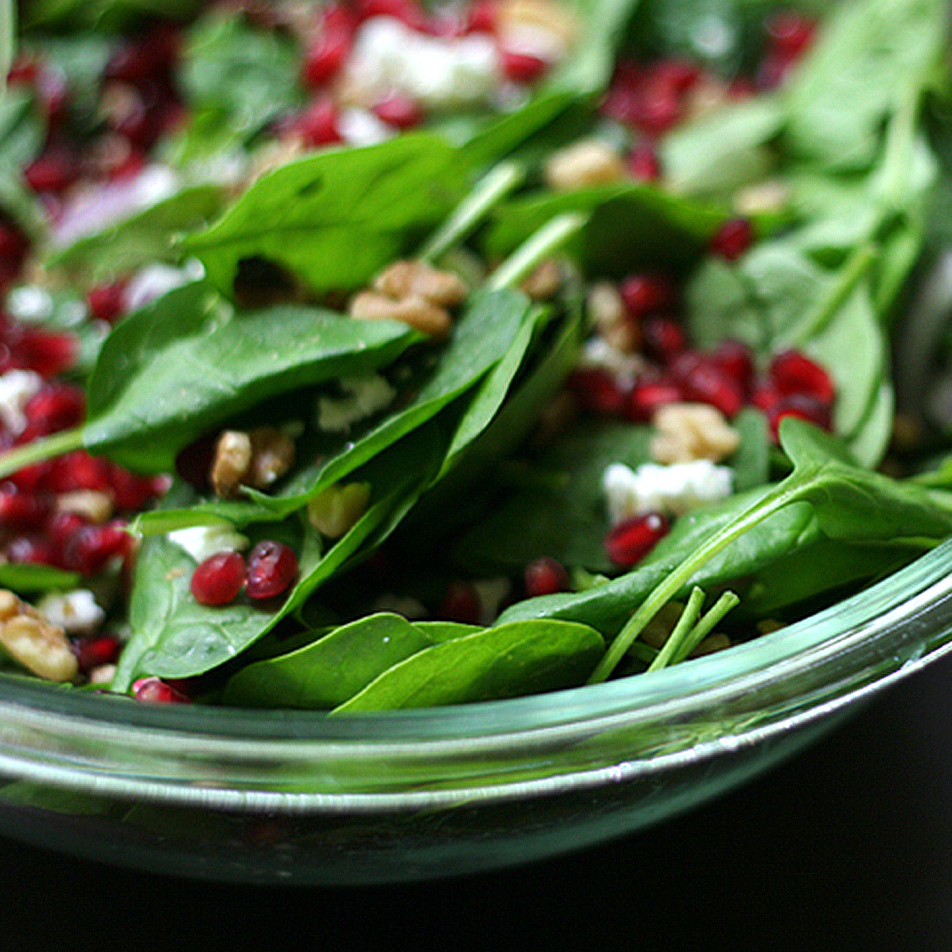 spinach and pomegranate salad in a glass bowl
