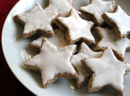 a German Christmas cookie cut into star shapes with a thin white glaze on a white plate