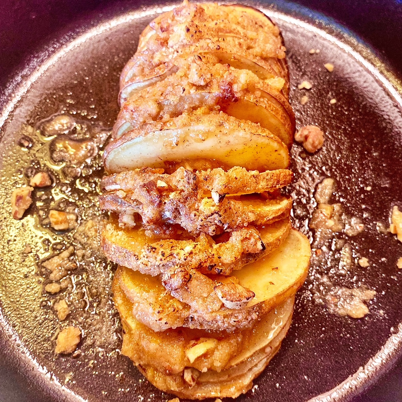 hasselback sweet potato with streusel topping in a skillet