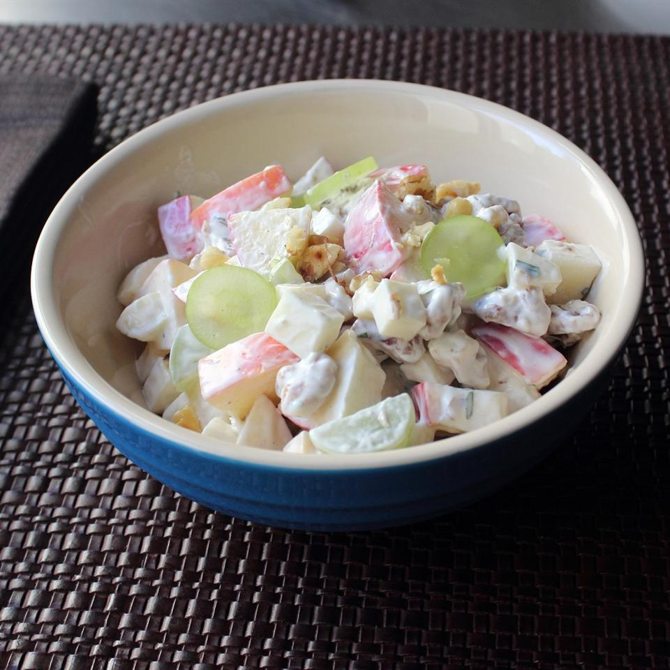 a salad of chopped apple, celery, and walnuts in a small blue bowl with a white interior