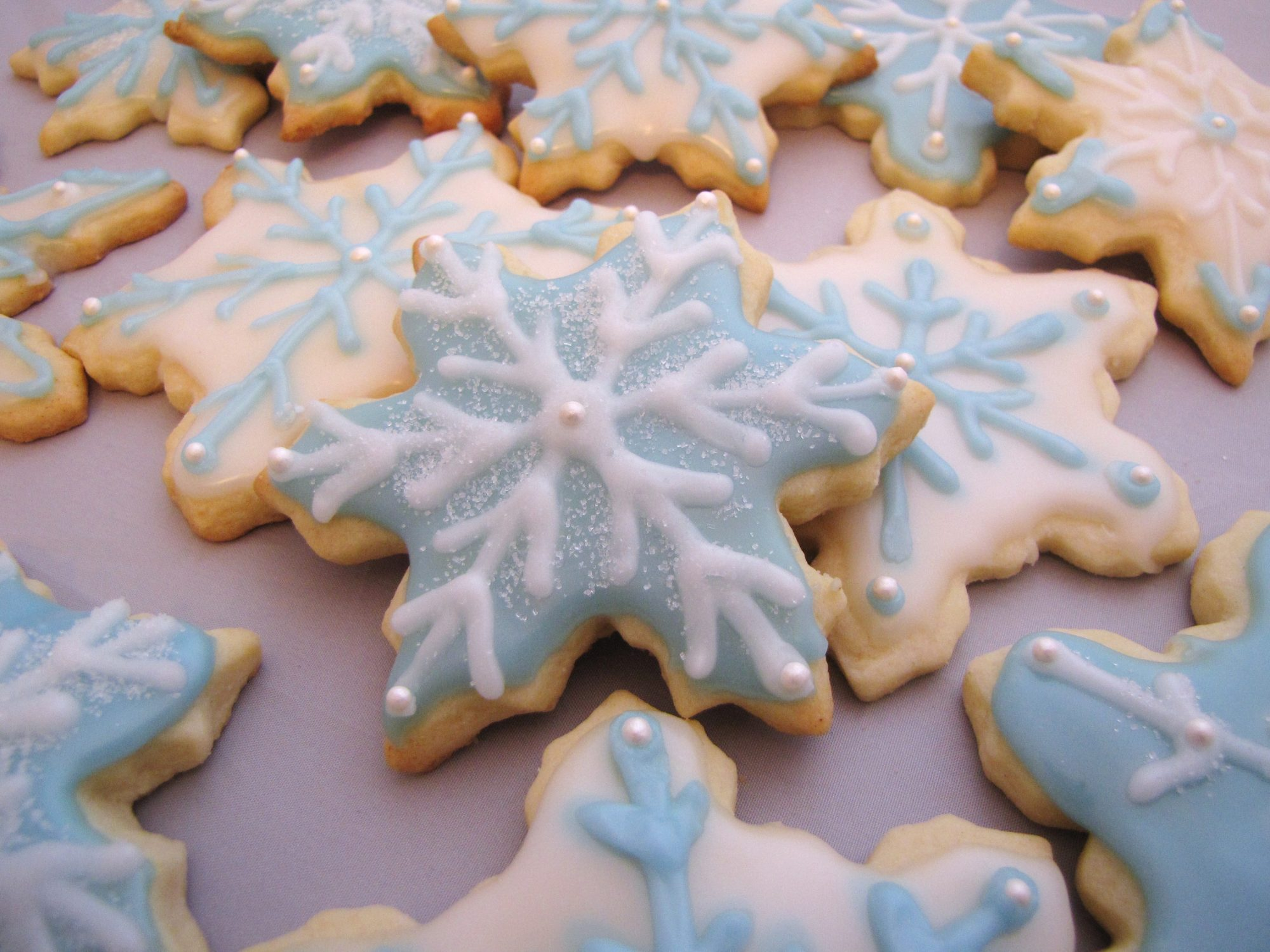 snowflake-shaped cookies decorated with pale blue and white icing