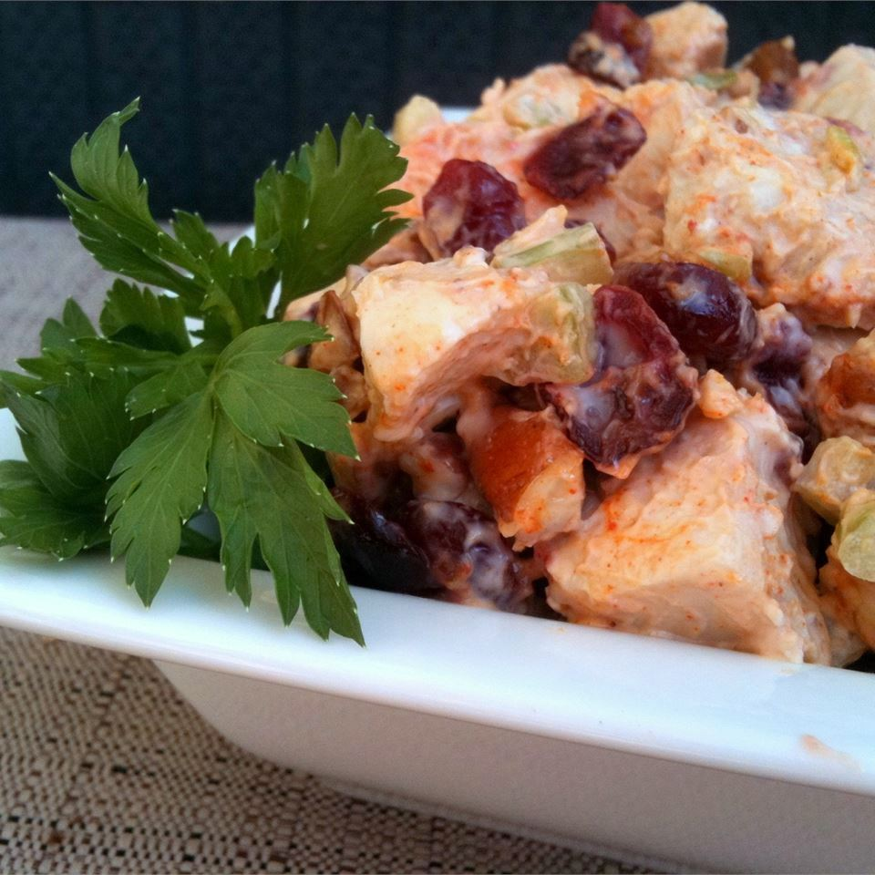 chicken salad with cranberries and parsley garnish in a white dish