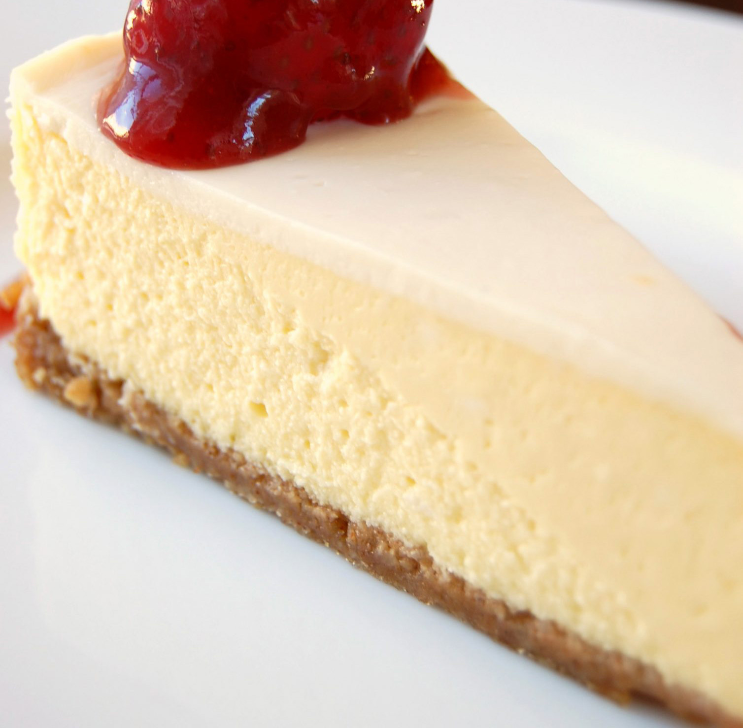 closeup of a slice of cheesecake with a thin sour cream layer and glazed strawberry on top