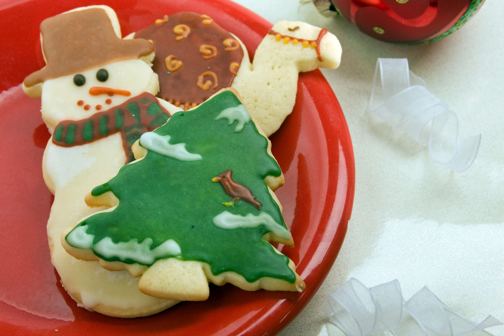 three cookies on a red plate: a snowman wearing a scarf and brown top hat, an evergreen with snow and a cardinal on its boughs, and a camel