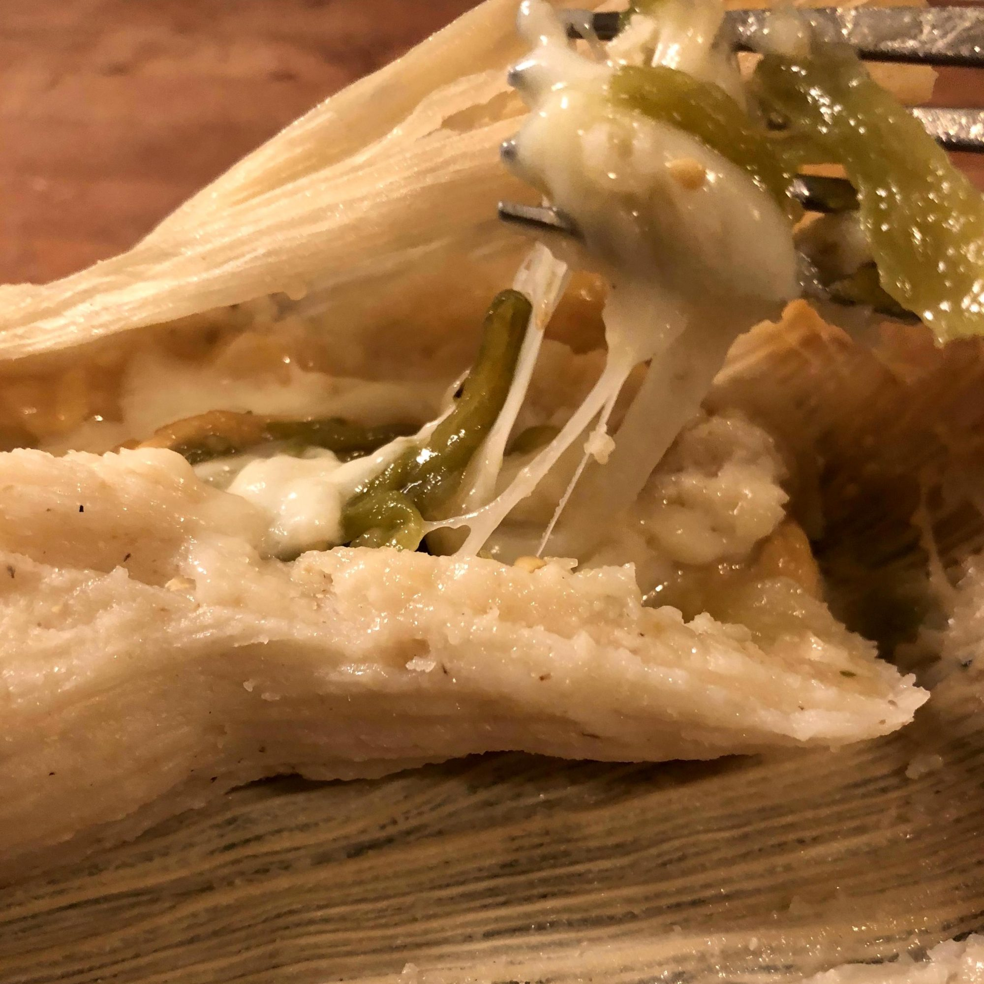fork cutting into poblano and cheese tamales