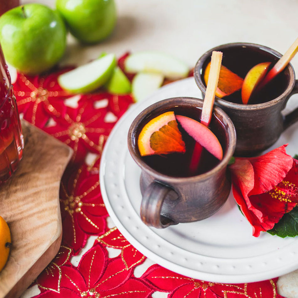 two mugs of ponche punch garnished with orange wedges