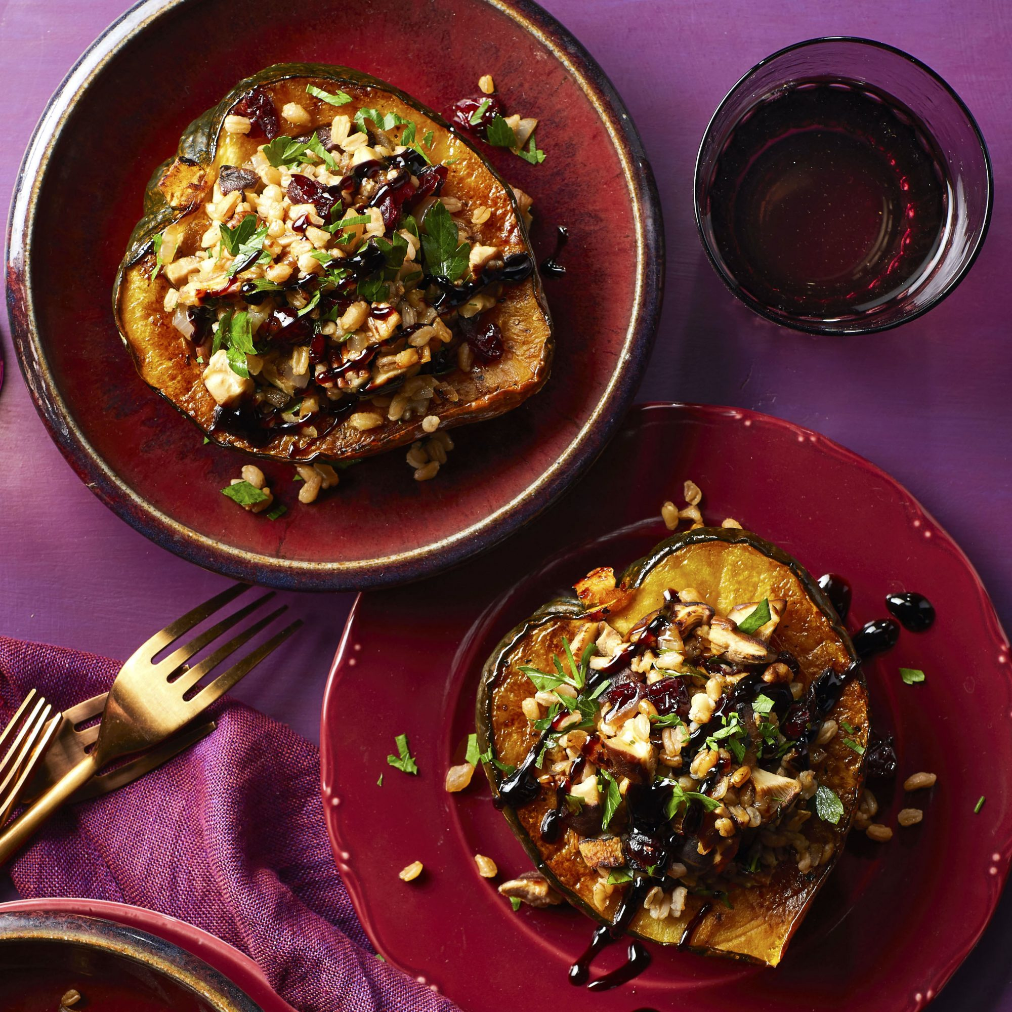 two plates of roasted acorn squash halves with farro stuffing