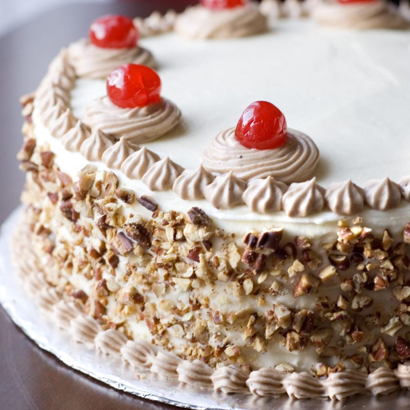 Italian Cream Cake decorated with chopped nuts and cherries