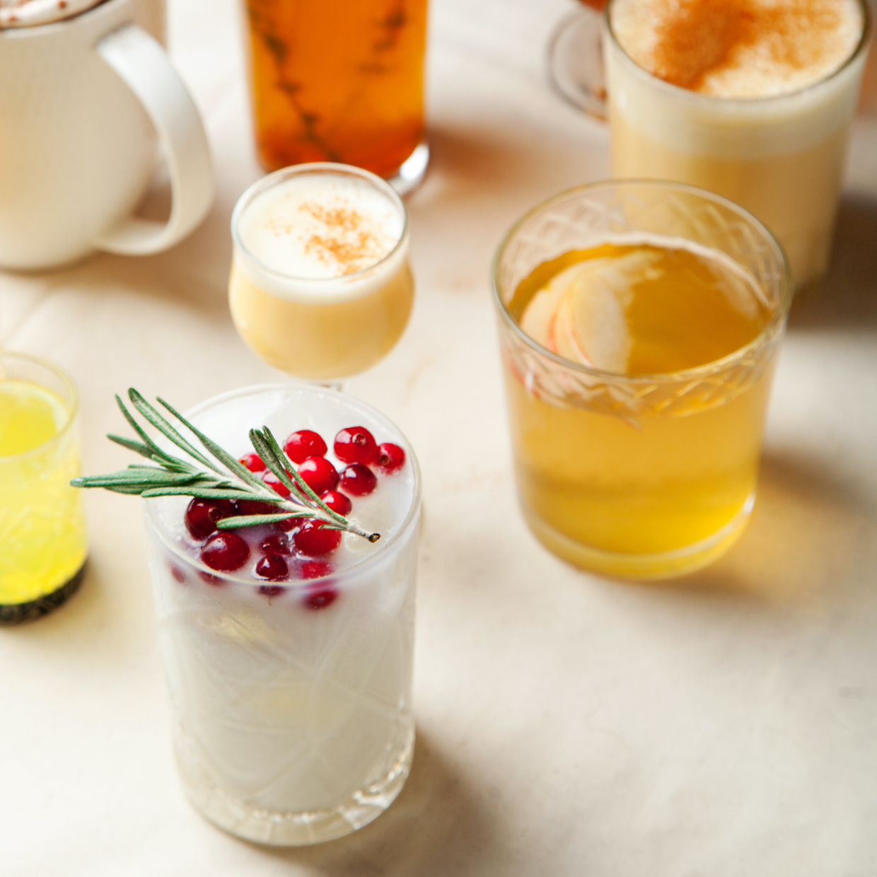 Set of various winter cocktails: mulled wine, eggnog, limoncello, old-fashioned, coconut margarita.