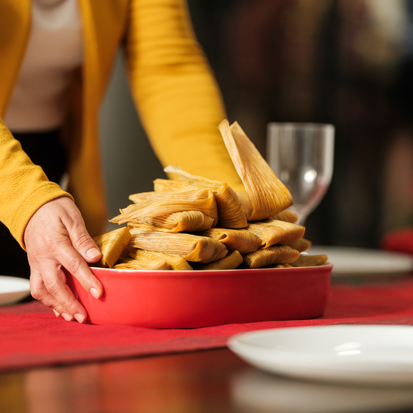 woman putting tamales on a table for Christmas