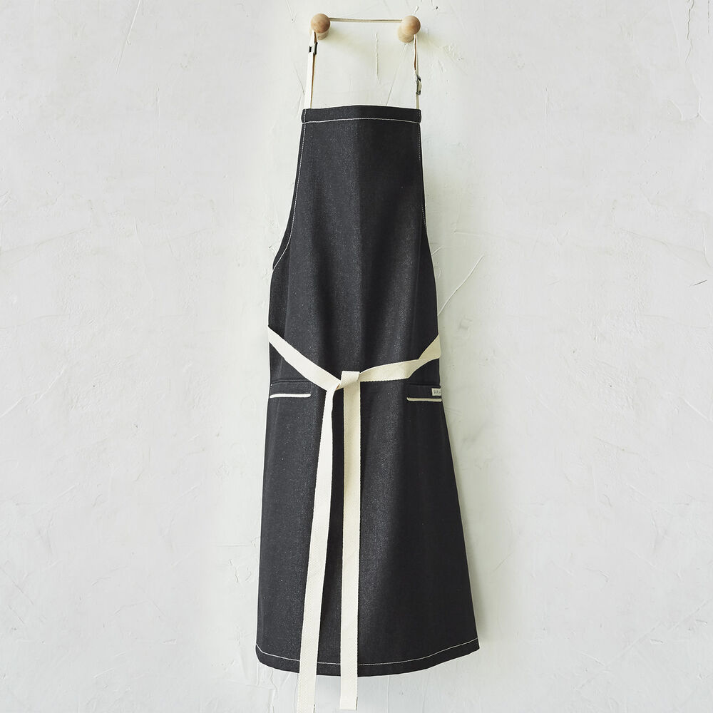 Black apron with white stitching and straps hanging from coat hook