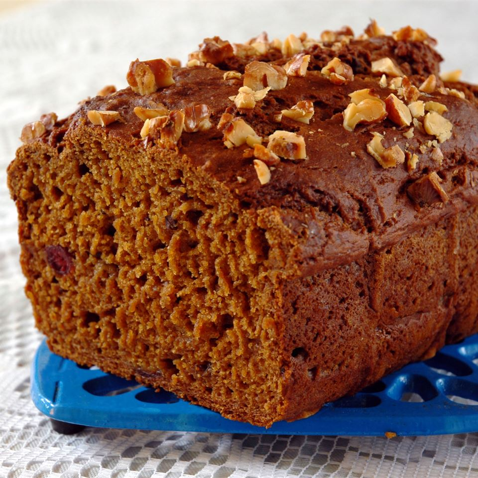 loaf of cranberry pumpkin bread topped with crushed walnuts