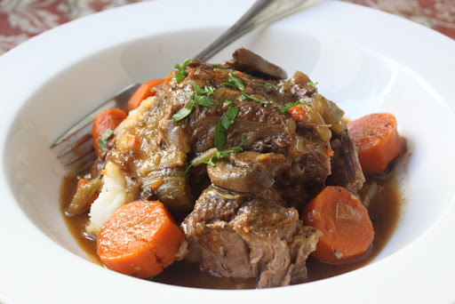 closeup of a shallow bowl filled with pot roast and carrots on mashed potatoes, garnished with parsley