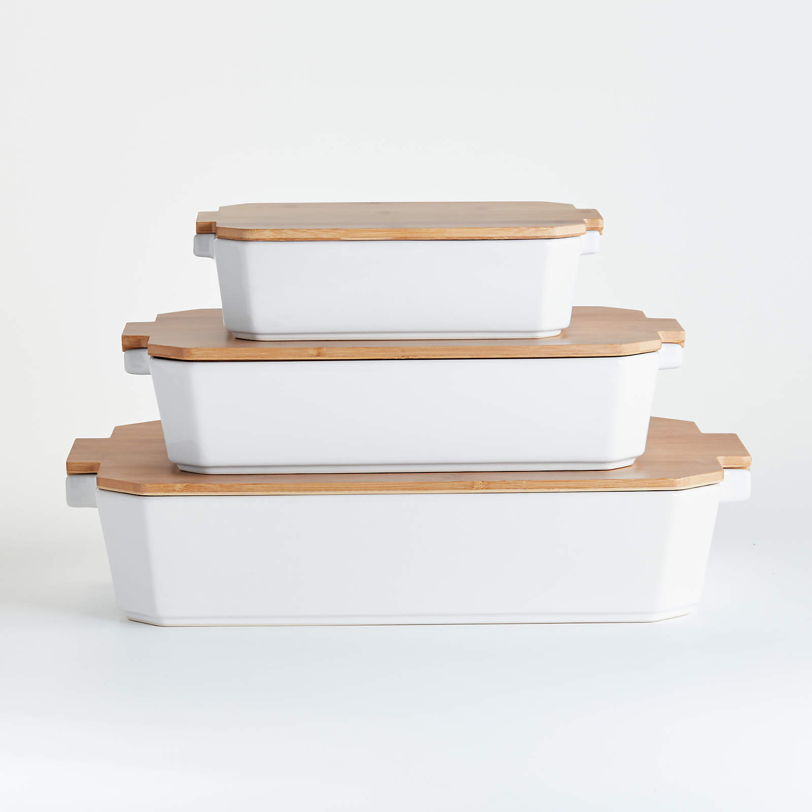 set of three white stoneware baking dishes with bamboo lids