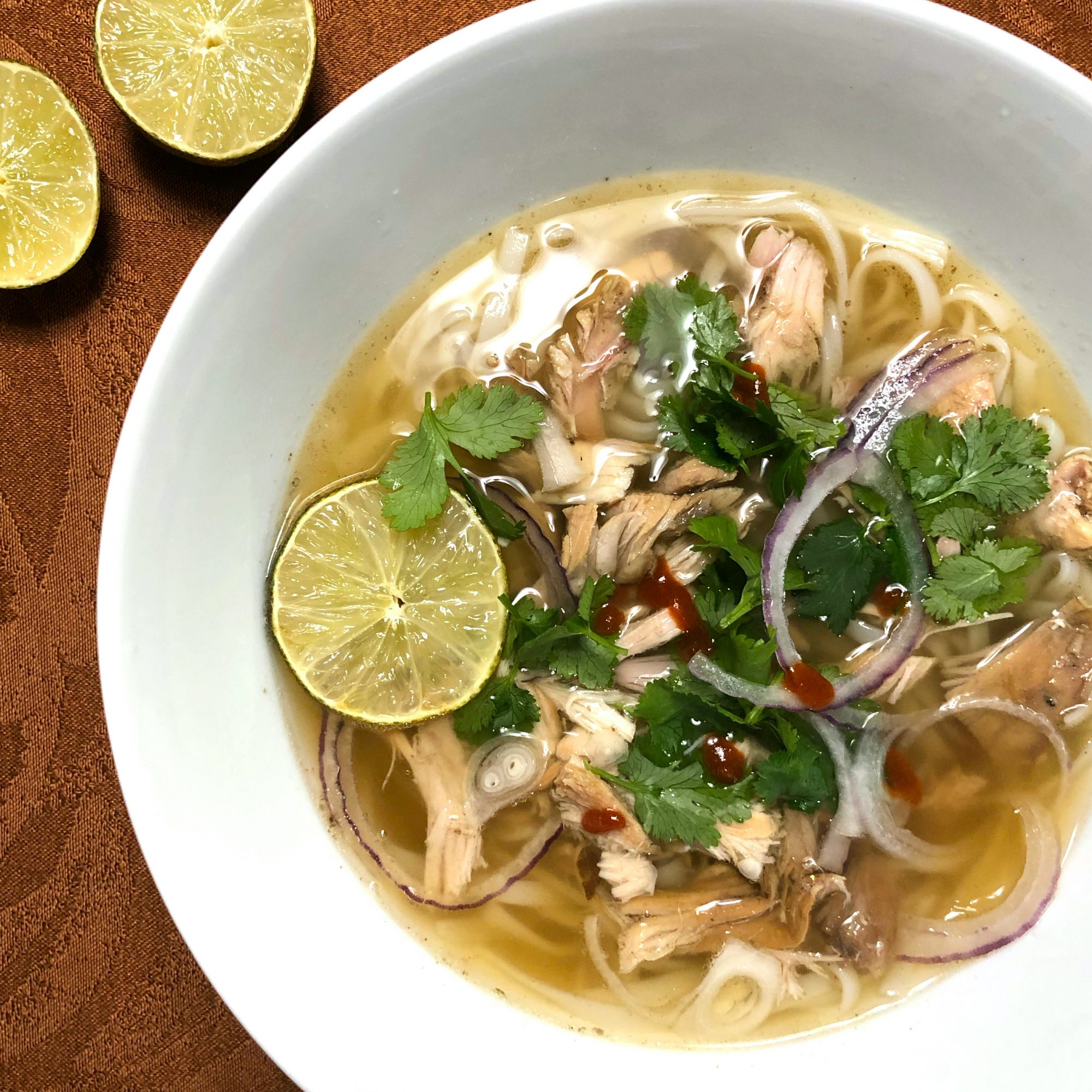 bowl of turkey pho with sliced limes on the side