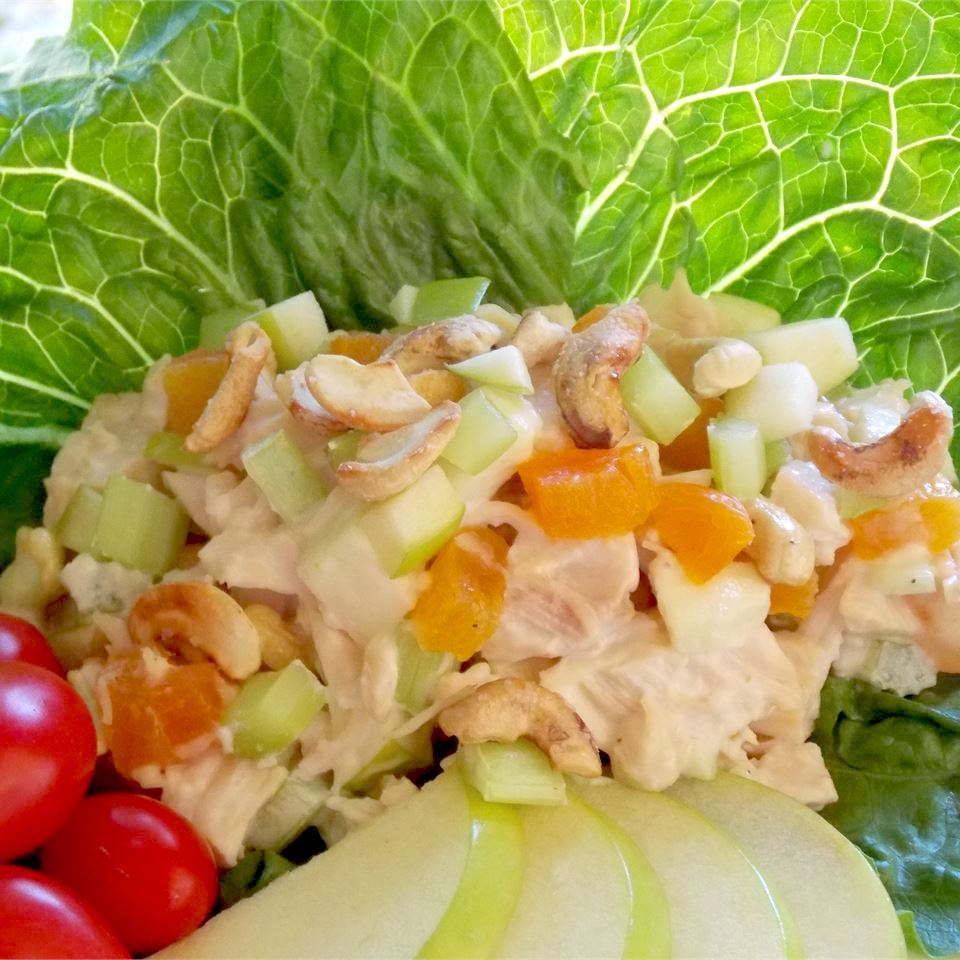 turkey salad with apricots, celery served in lettuce with cherry tomatoes and apple slices
