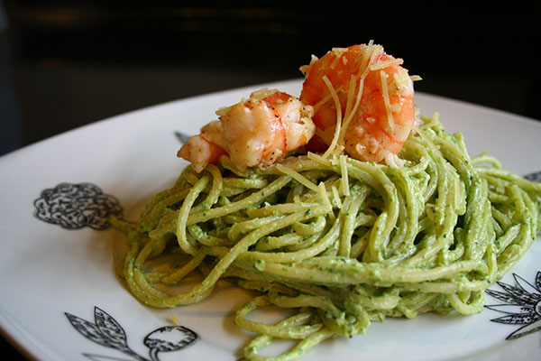 a serving of pale green pesto-coated pasta topped with shrimp on a white plate with a black background