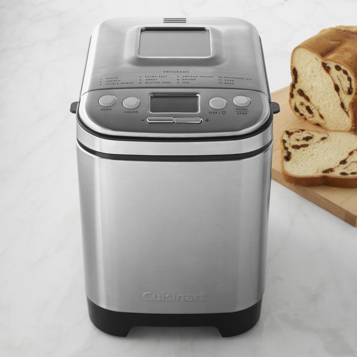 Stainless steel bread maker on countertop next to loaf bread