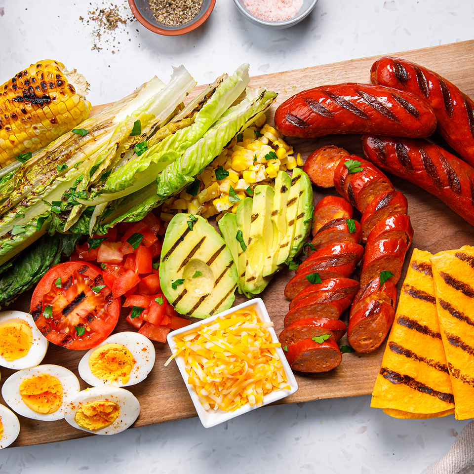 Grilled cobb salad on a cutting board with sausages and avocado