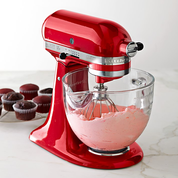 Red KitchenAid mixer with glass bowl, pink batter inside