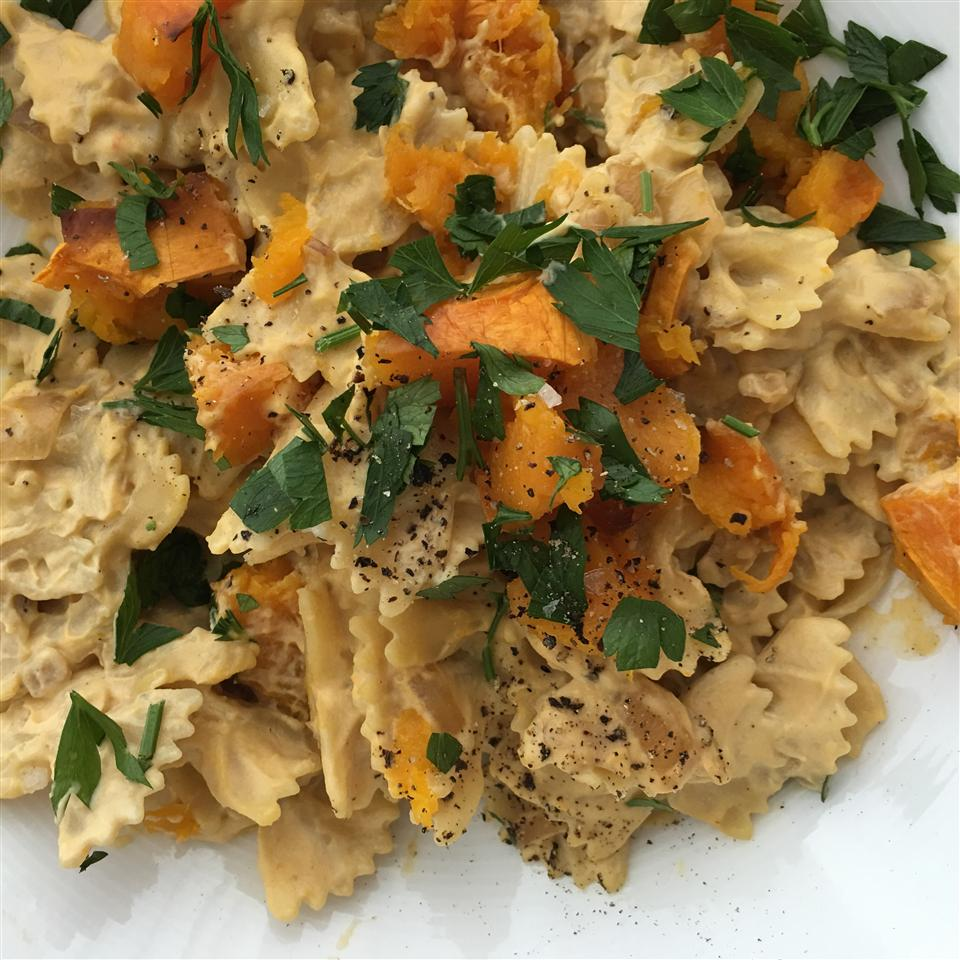 plate of farfalle pasta with butternut squash and alfredo sauce topped with chopped parsley