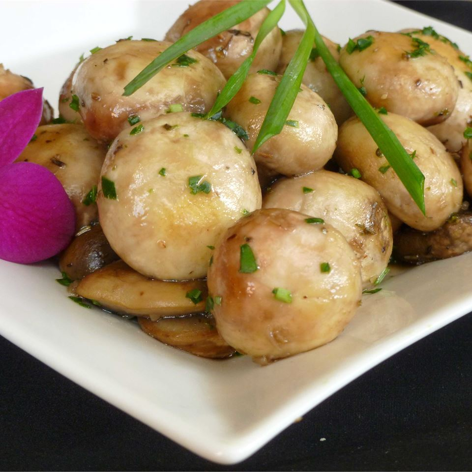 buttery herbed mushrooms on white plate