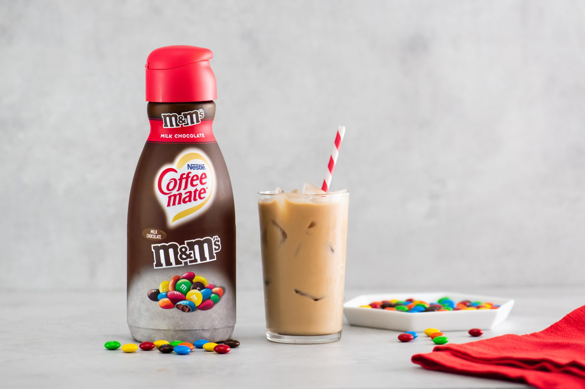 A bottle of coffee creamer next a glass of iced coffee