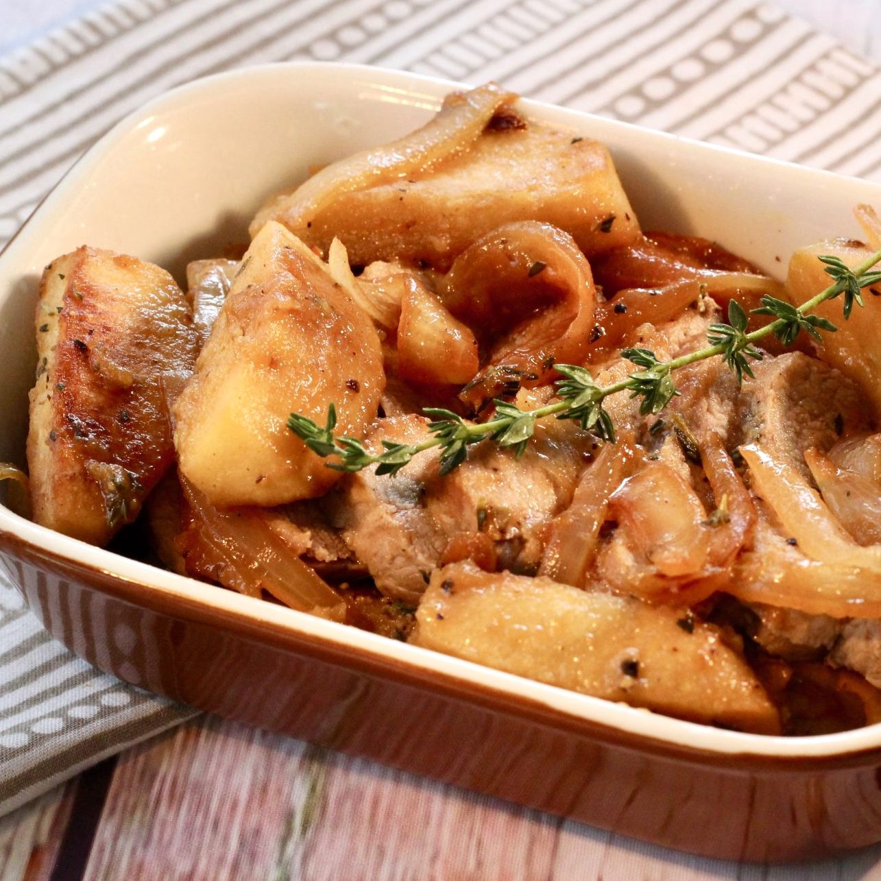 pork tenderloin and apples in a dish with thyme on top