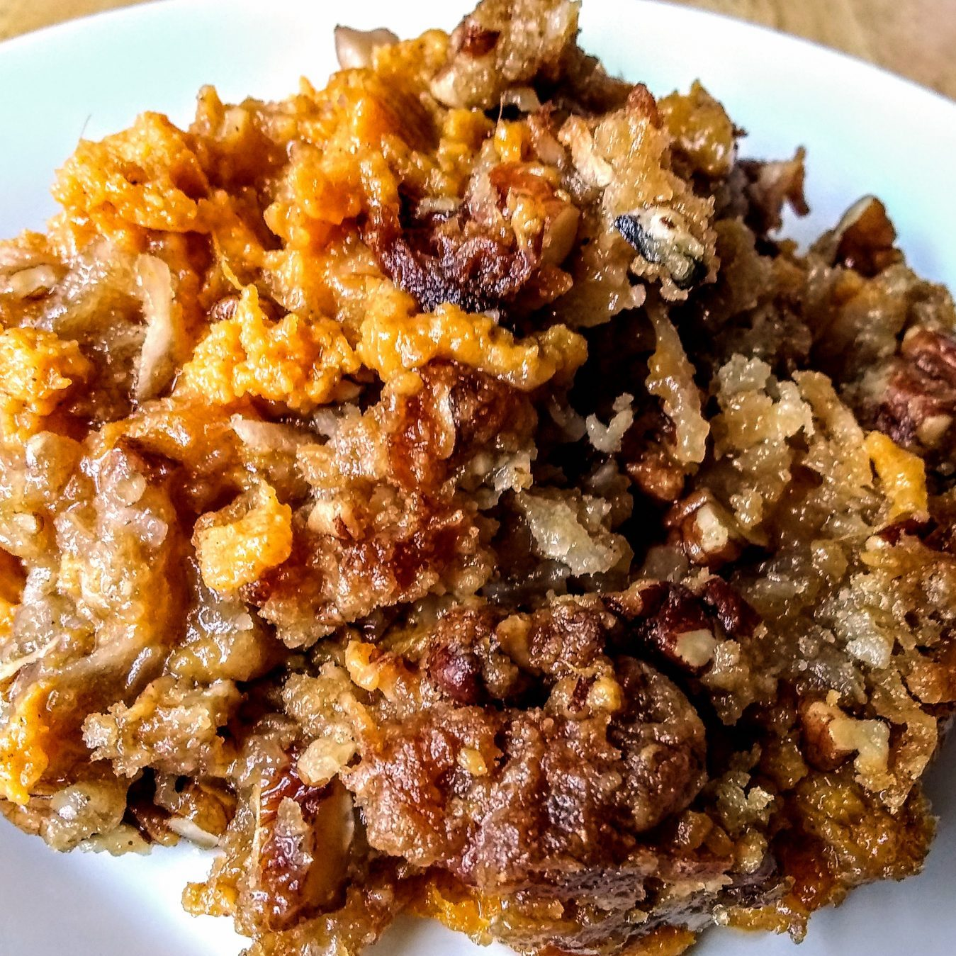sweet potato casserole with streusel coconut topping on a white plate