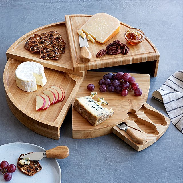 Wooden swivel cheese board with charcuterie makings on top