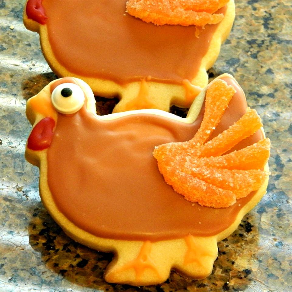 Thanksgiving cookies decorated to look like turkeys with a sliced orange jelly candy tail