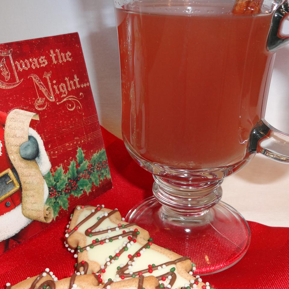wassail in a glass mug beside a Christmas cookie