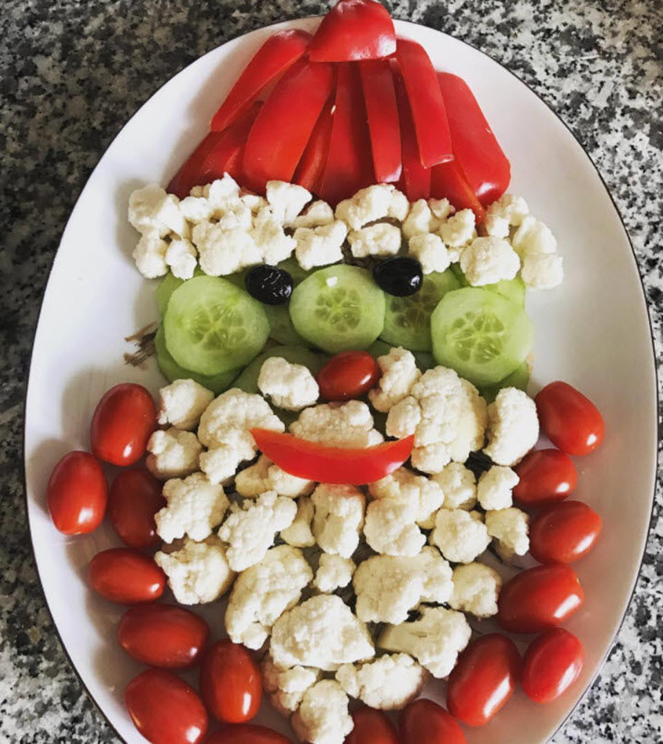 tomatoes, cauliflower, cucumbers, and bell pepper in the shape of Santa's head