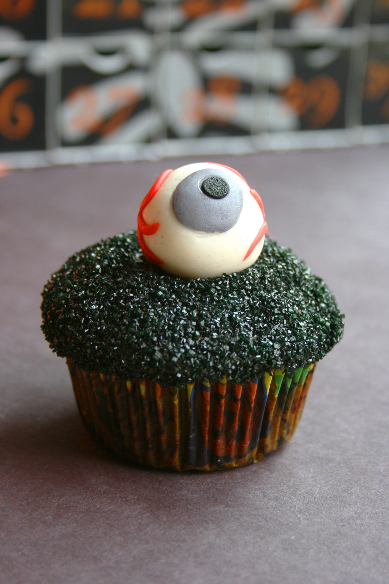 a single cupcake decorated for Halloween with a bloodshot eyeball made of fondant on top