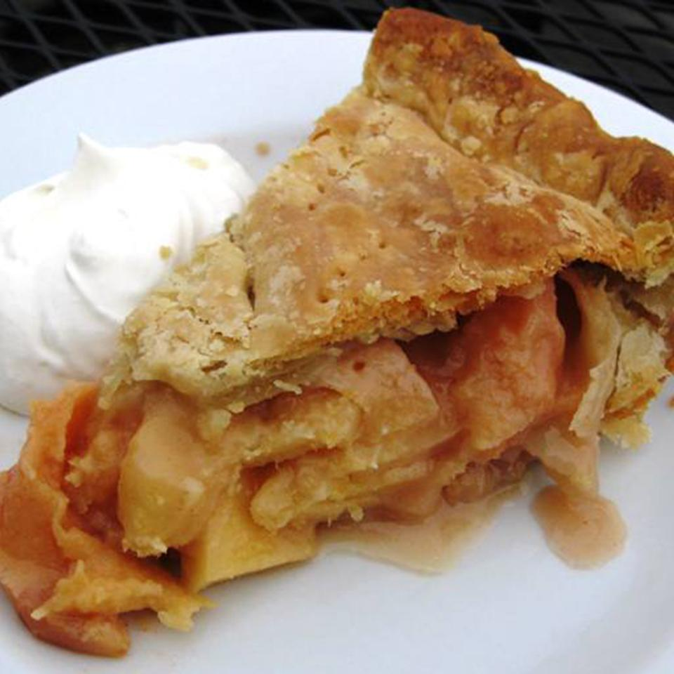 a slice of two-crust fruit pie with a rosy-tinted filling, with whipped cream on the side