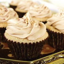 side view of a tray of cupcakes in dark brown paper liners with a cream-colored frosting