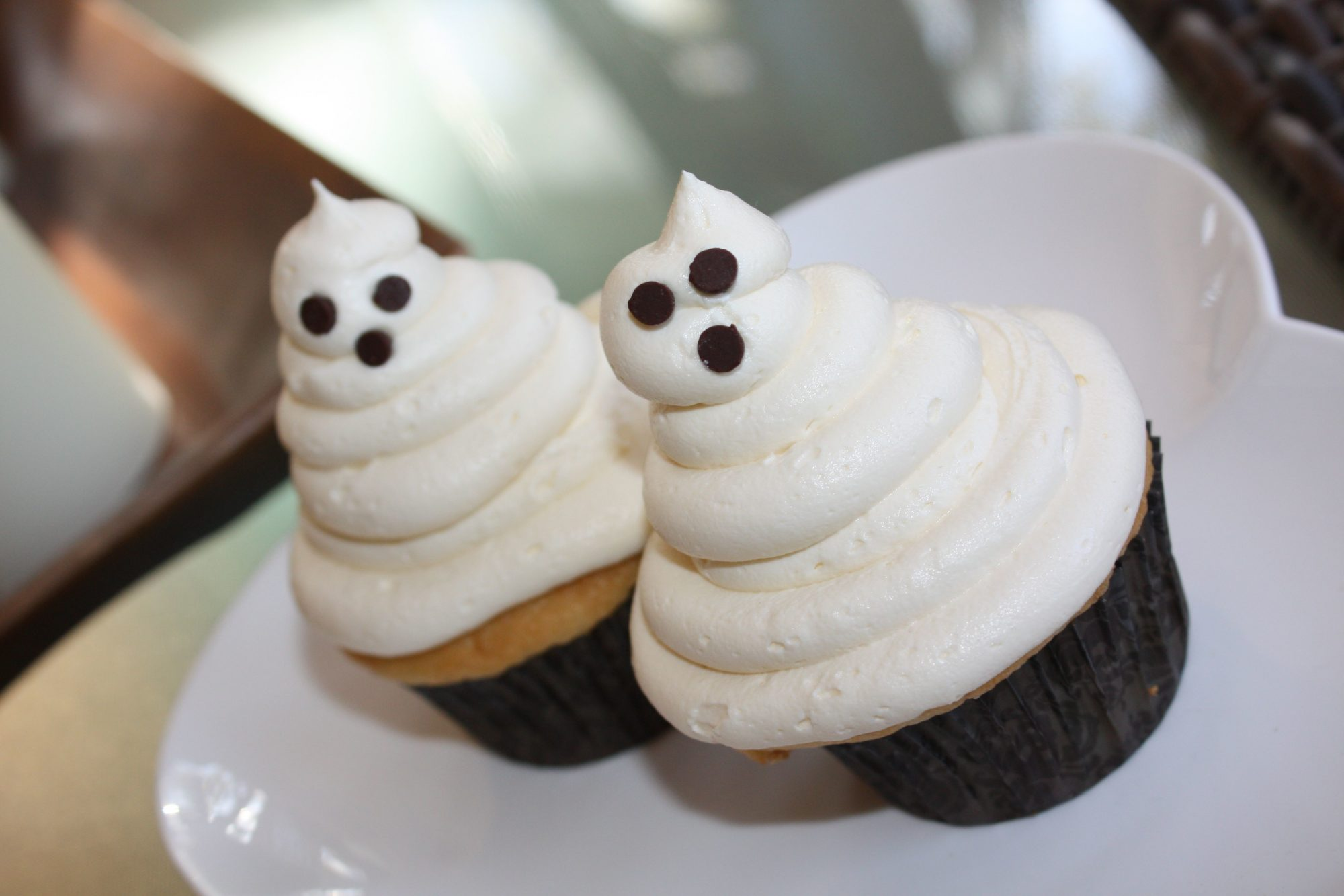 two Halloween cupcakes decorated to look like ghosts