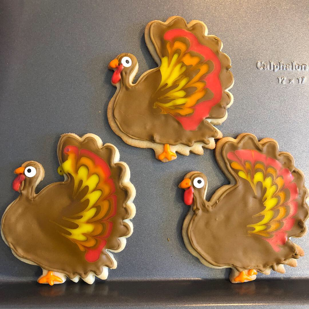 three colorfully decorated Thanksgiving turkey cookies on a sheet pan with brown bodies and marbled yellow, orange, and red tail feathers on a baking sheet