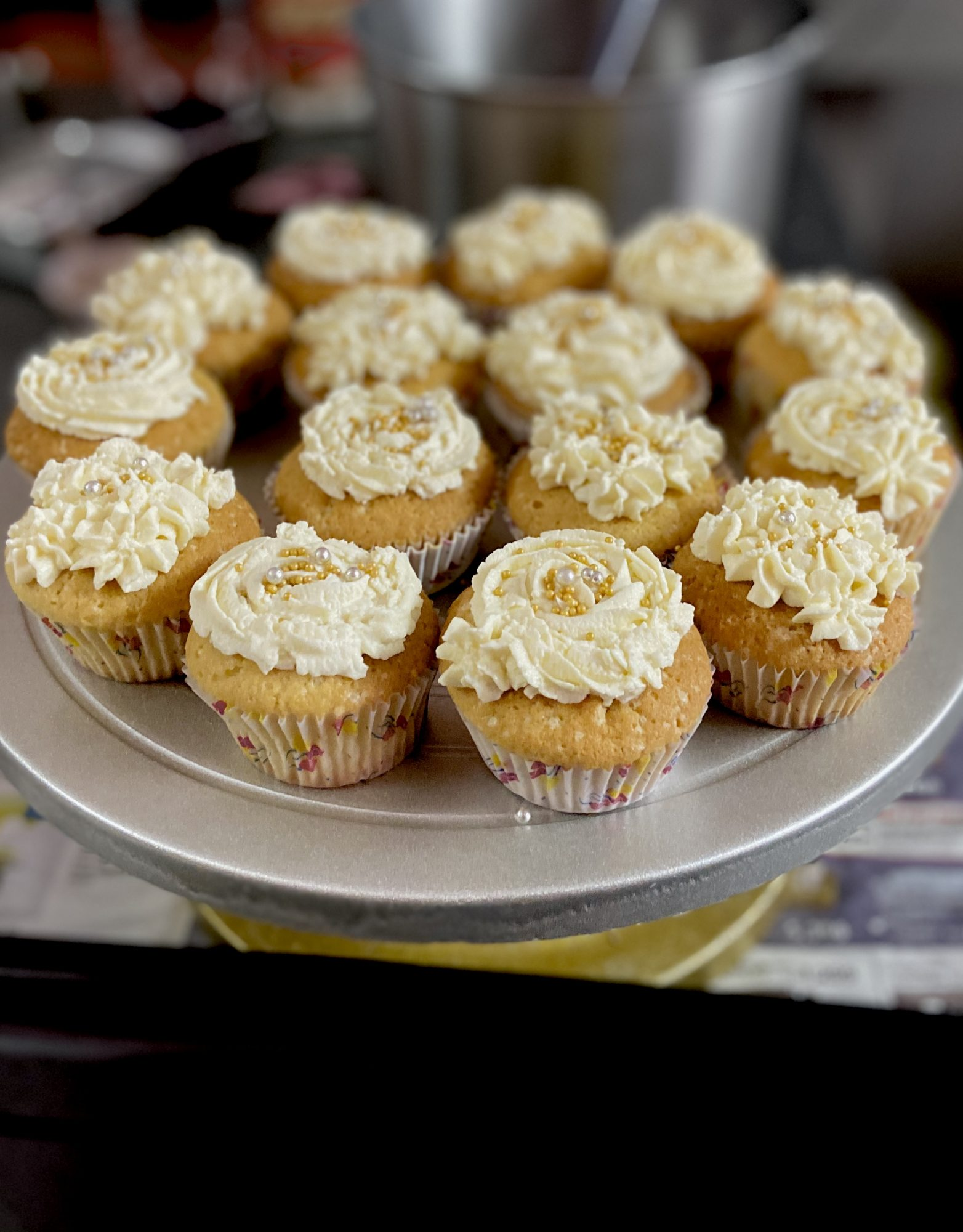 a plate holding 15 cupcakes with piped white frosting and gold sprinkles