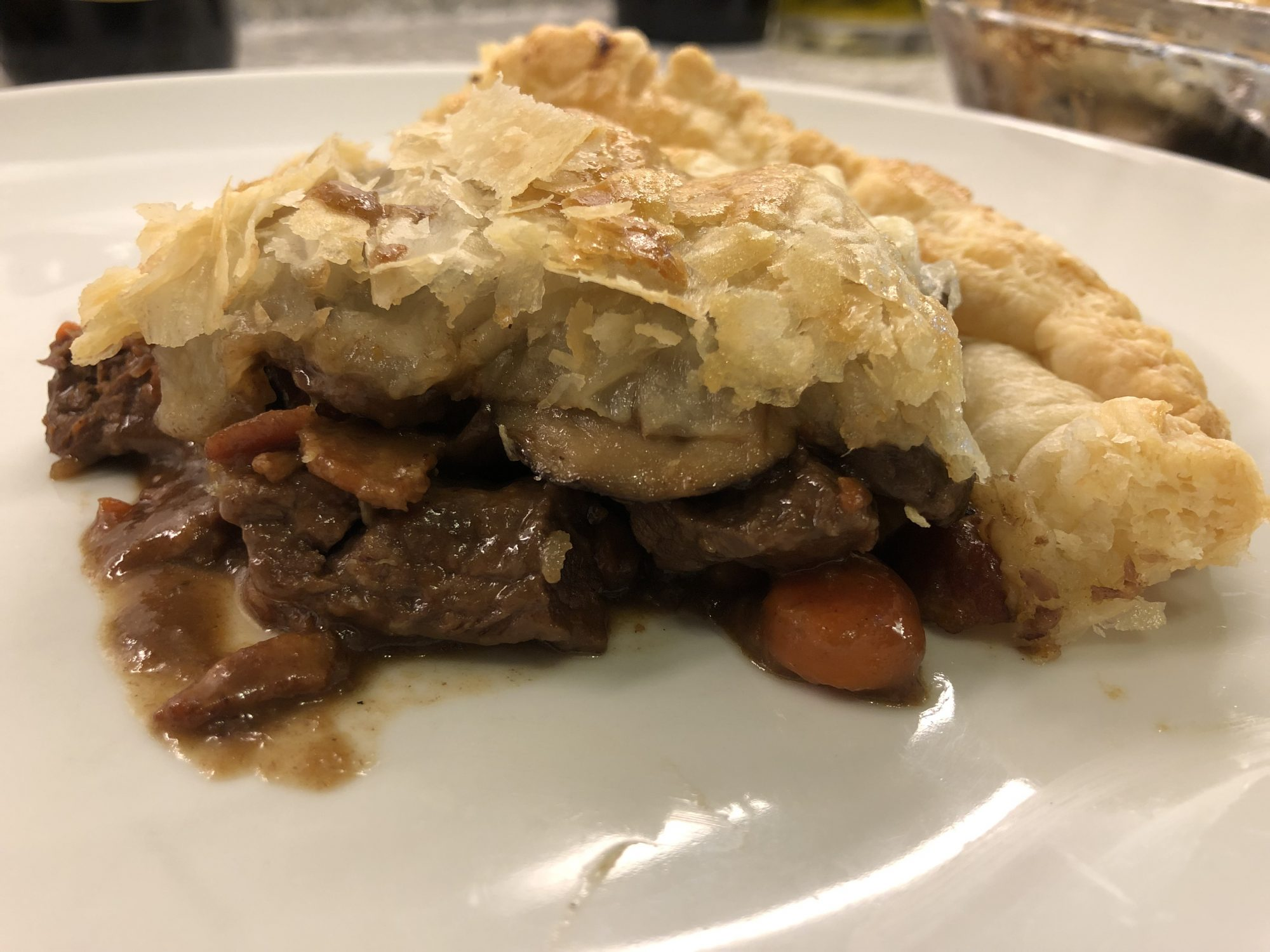 Slice of beef and mushroom pie with flaky crust