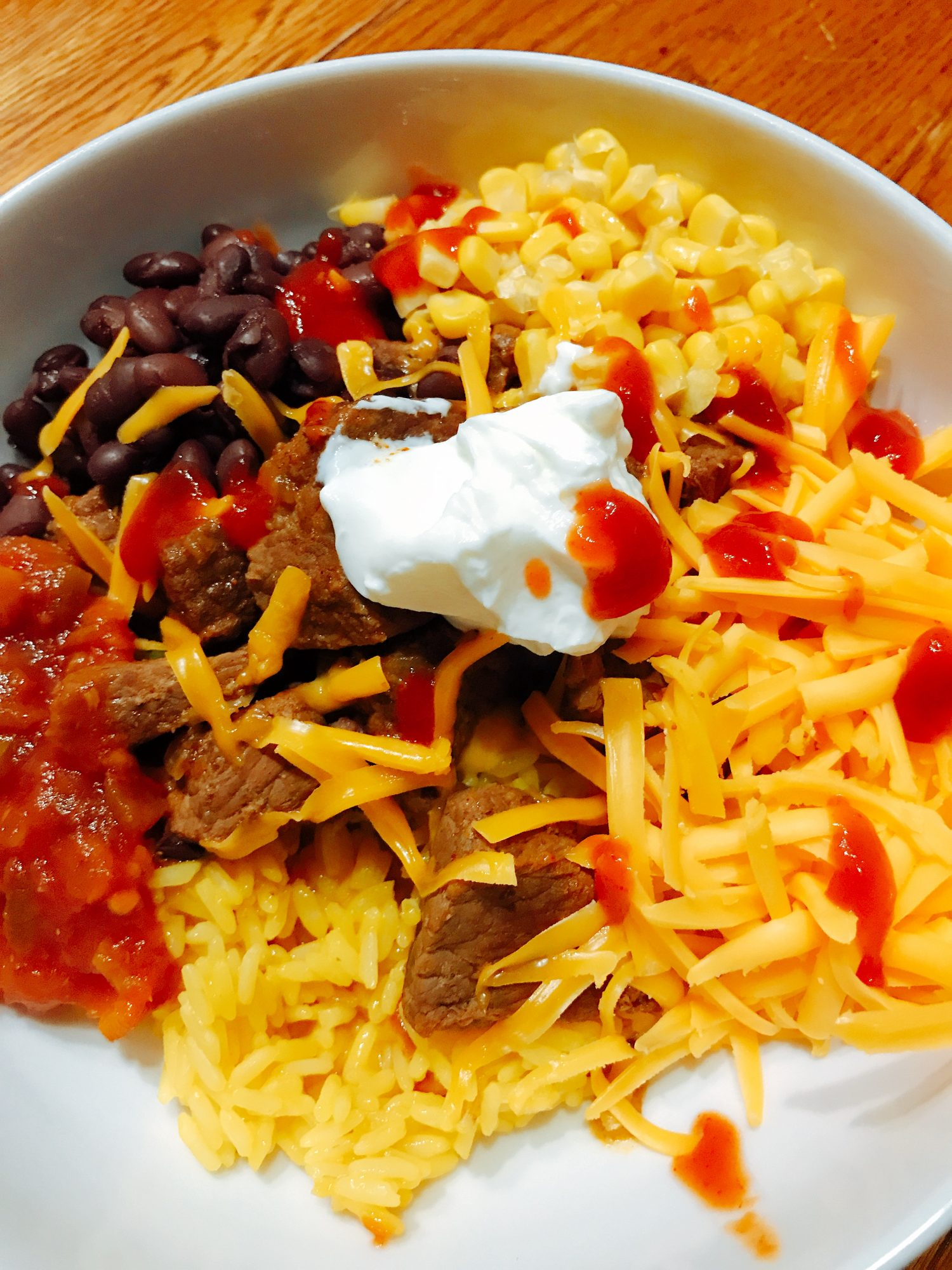 Rice, beef, cheese, salsa, black beans, and corn in white bowl