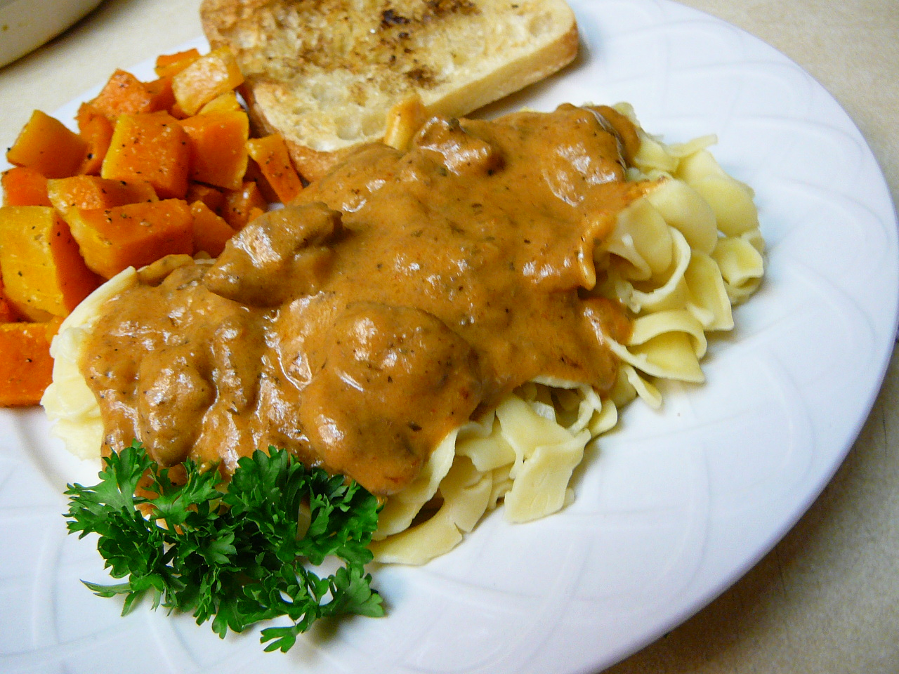 Beef tips with sauce over pasta with carrot side dish