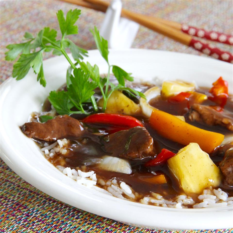 Sweet and sour beef over rice in white bowl