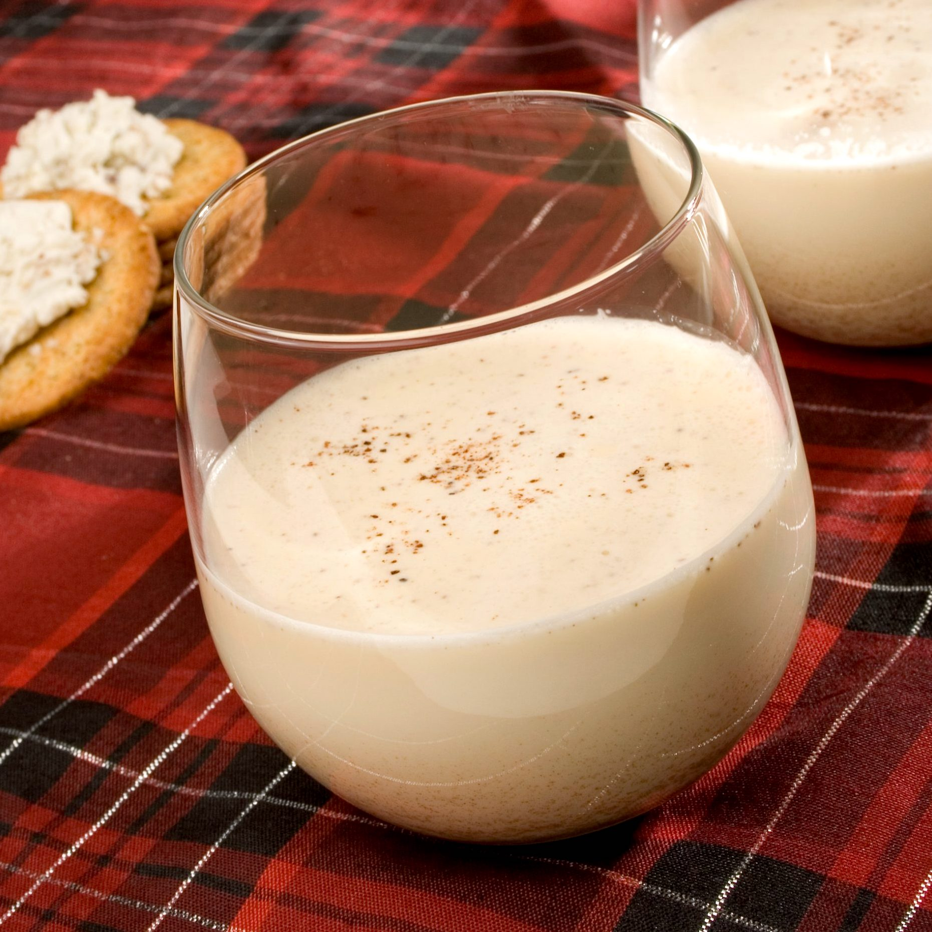 two glasses of eggnog on a red plaid tablecloth